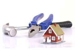 Pliers, hummer and little house over white. Royalty Free Stock Photo