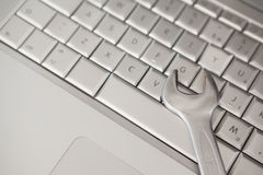 Pliers lying on silver keyboard Stock Photography