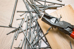 Pliers and nails. On wooden panel Royalty Free Stock Images