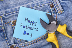 Pliers near Father`s Day card. Jeans pocket with pliers. Masculine present for best daddy Stock Image