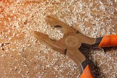 Pliers on old crafting table, withe orange handle and metal filings stock photography