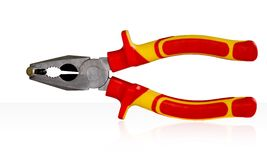 Pliers. A pair of silver metal pliers with red and yellow rubber grips isolated on white stock photo