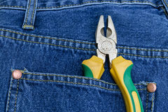 Pliers of pocket jeans. Pliers to repair a pocket of jeans royalty free stock photo
