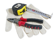 Pliers red and black color, dirty leather gloves and tape measur Stock Photography