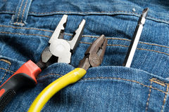 Pliers and screwdriver on bag jean background Royalty Free Stock Photo