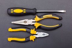 Pliers and screwdriver on black Stock Image