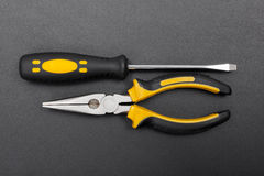 Pliers and screwdriver on black Royalty Free Stock Images