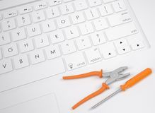 Pliers and screwdriver on the keyboard Stock Photo