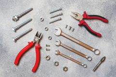 Pliers, screwdrivers and wrench combination on grey concrete background with copy space. Professional ergonomic repair tools.  royalty free stock image