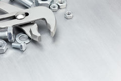 Pliers, screws and bolts of different size for work on scratched Royalty Free Stock Images