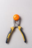 Pliers and tangerine Stock Photos