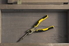 A pliers tool with bolt on a wooden furniture surface. As background stock photo