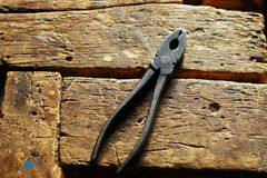 Pliers on the wooden table Stock Photography