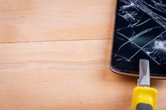 Pliers clamp smartphone with a broken screen. On a wooden surface. Pliers with a yellow pinched clamp modern black smartphone with a broken screen. On a wooden stock images