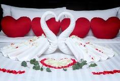 Pliez un cygne de serviette pour des décorations avec des pétales de rose sur le lit Photographie stock libre de droits