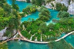 PLITVICE, CROÁCIA - 29 DE JULHO: O turista aprecia sightseeing os lagos e as paisagens maravilhosas no parque natural de Plitvice Imagens de Stock