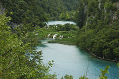 Plitvice national park. Multiple beautiful waterfalls surrounded by exuberance of vegetation fall down from one turquoise lake into another Stock Photos