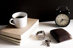 Plånbok, klocka och nyckel- kedja bredvid en kopp kaffe på boken Arkivfoton