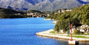 City of Ploce north bay. Ploce,  Ploče, north bay viewed from ferry dock. lighthouse and sea in foreground Royalty Free Stock Photo