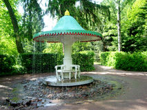 Plocka svamp springbrunnen som omges av stenar i parkera av Peterhofen arkivfoto