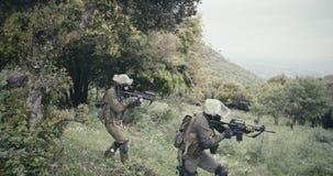 Ploeg van volledig bewapende commandomilitairen tijdens gevecht in een boslandschap stock footage