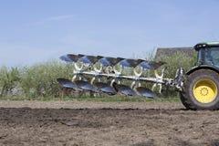 Plog bak traktoren på holländskt fält i Nederländerna i vår nära utrecht Arkivbilder