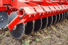 Ploga det röda traktorslutet för modern tech upp på ett jordbruks- fält royaltyfri bild