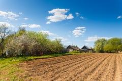plogat fält på en bakgrund av lantliga hus Royaltyfri Fotografi
