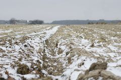 Plogat land i vinter med djupa fåror som strilas med snö arkivbild