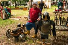 Ploiesti, Roemenië - Juli 14, 2018: De acteur kleedde omhoog de strijder van ottomaneturk stelt omringd door middeleeuwse wapens, stock foto