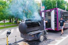Ploiesti, Roemenië - Juli 14, 2018: De mens woont barbecue, de oven van het rookhuis in vorm van treinlocomotief bij bij het Midd royalty-vrije stock foto's