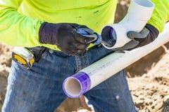 Plombier Applying Pipe Cleaner, amorce et colle dans des tuyaux de PVC images libres de droits