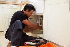 Plombier de métis fixant l'évier de cuisine dans une maison Images stock