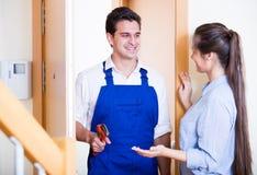Plombier de salutation de femme au foyer à la porte de maison Photographie stock libre de droits