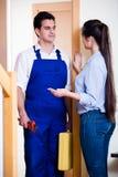 Plombier de salutation de femme au foyer à la porte de maison Image libre de droits