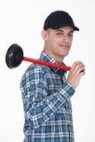 Plombier de sourire tenant le plongeur Photo stock