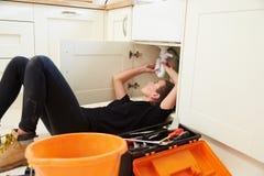Plombier féminin fixant un évier de cuisine photos stock