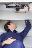 Plombier fixant le tuyau photographie stock libre de droits