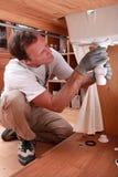 Plombier fixant un évier Photos libres de droits