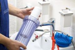Plombier installant le nouveau système de filtration de l'eau image stock