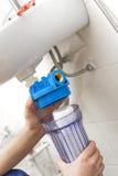 Plombier installant le nouveau système de filtration de l'eau photos stock