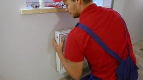 Plombier installant le radiateur de chauffage sur le mur banque de vidéos