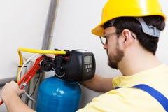 plombier installant le système de filtration de l'eau image libre de droits