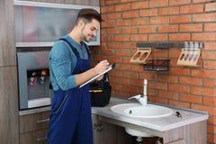 Plombier masculin avec le presse-papiers pr?s de l'?vier de cuisine images stock