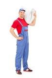 Plombier portant une cuvette des toilettes Photos stock