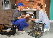 Plombier professionnel avec le client féminin près de l'évier de cuisine photo libre de droits