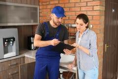 Plombier professionnel dans l'uniforme avec le client féminin à l'intérieur photo libre de droits