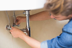 Plombier réparant le drain de lavabo à la salle de bains Images stock