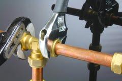 Plombier serrant la canalisation Images libres de droits