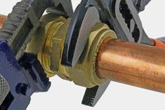 Plombier serrant la canalisation Photo stock